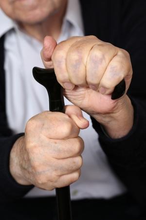 senior adult man: Hands of an old senior adult man holding on a crutch