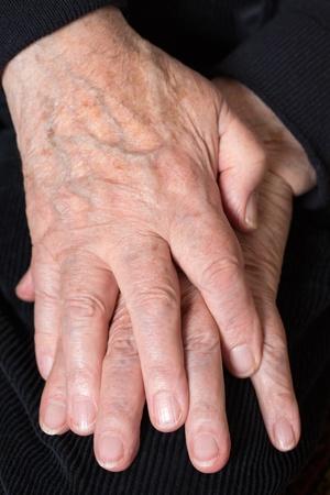 mani incrociate: Un vecchio adulto senior si tiene le mani incrociate