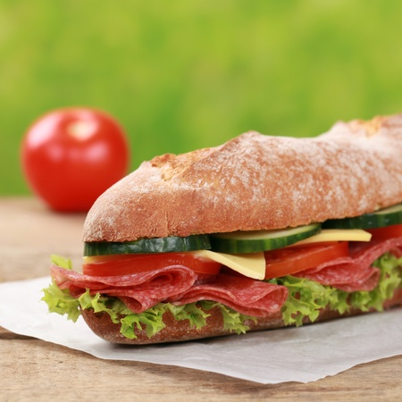 Baguette with salami, cheese and lettuce, garnished with a tomato