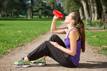 Young woman takes a break for drinking water after sports or running photo