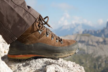 hiking shoes: Hiking boots of a hiker on a rock in the mountains