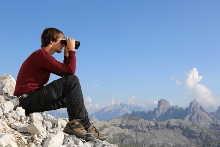 Young man looking through binoculars in the mountains