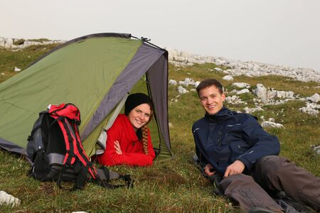 Two young people camping in the mountains alps photo