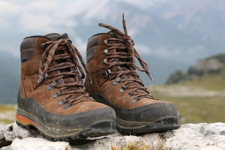hiking shoes: Hiking shoes of a hiker on a rock in the mountains Stock Photo