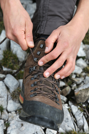 hiking boots: Tying the hiking boots of a hiker on a rock in the mountains Stock Photo
