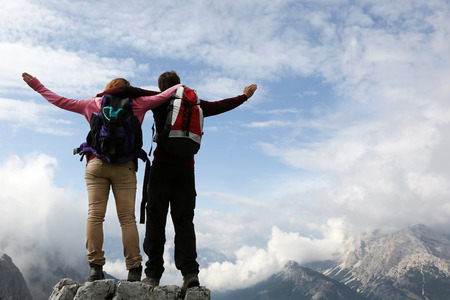 Two young mountaineers standing on mountain top and enjoying their success photo