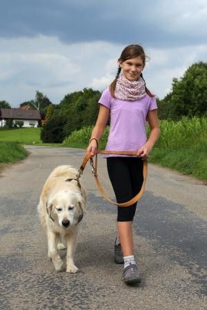 Klein meisje lopen haar hond buiten in de natuur