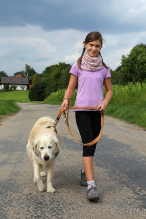 Little girl walking her dog outdoors in nature photo
