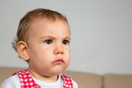 angry baby: Portrait of a sad or angry looking baby Stock Photo