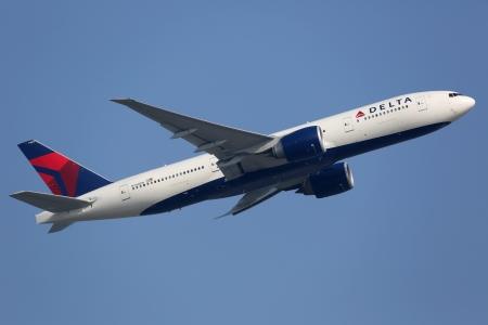 Hong Kong, China - 26 september 2013: Een Delta Air Lines Boeing 777-200LR met de registratie N709DN neemt af van Hong Kong International Airport (HKG) in China. Delta Air Lines is 's werelds grootste luchtvaartmaatschappij met 733 vliegtuigen en een aantal 160 miljoen passe Stockfoto - 23787726