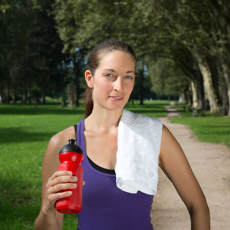 takes: Young woman with a drink takes a break during sports or running