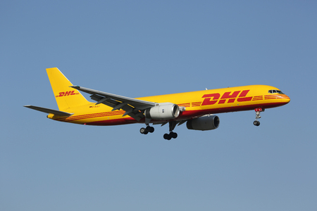 owned: Lisbon, Portugal - July 20, 2013: A DHL Boeing 757-200PF with the registration D-ALEJ on approach to Lisbon Airport (LIS) in Portugal. DHL is Europes largest cargo only airline and owned by Deutsche Post. It operates with 133 aircraft.