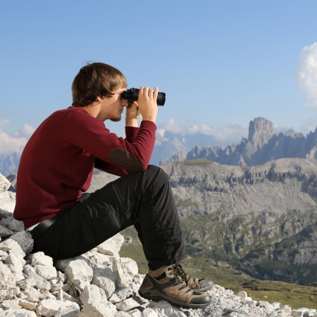 binoculars view: Young man looking through binoculars and searching the destination