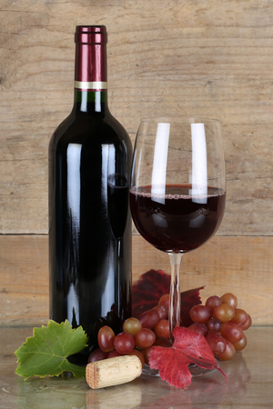 winetasting: Red wine in bottle and wineglass in front of a wooden background
