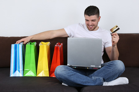 home shopping: A young man with shopping bags is using his laptop computer for internet shopping