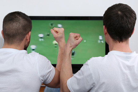 soccer fans: Young people watching football or soccer on tv