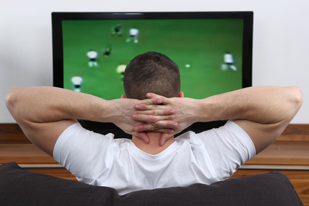 Young man sitting on a sofa and watching football or soccer on tv Stock Photo