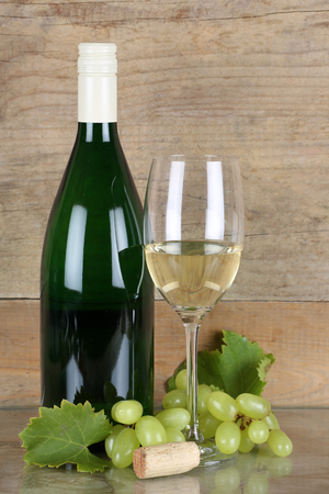 winetasting: White wine in a bottle and wineglass in front of a wooden background