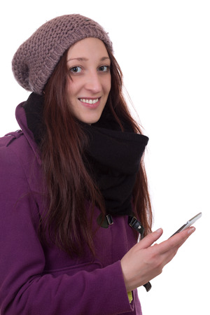 Young woman in winter with a mobile phone, isolated on a white background photo