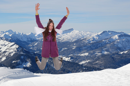 Young woman jumping for joy and happiness in winter in snow covered mountains photo