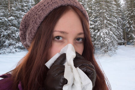 Young woman with a tissue having a cold and flu virus sneezing outdoors photo