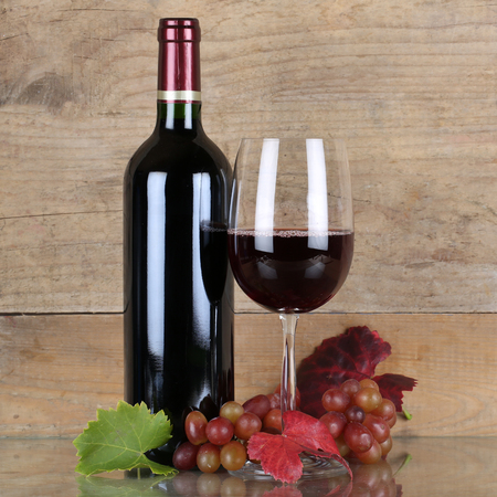 winetasting: Fresh red wine in wine bottle and glass in front of a wooden background