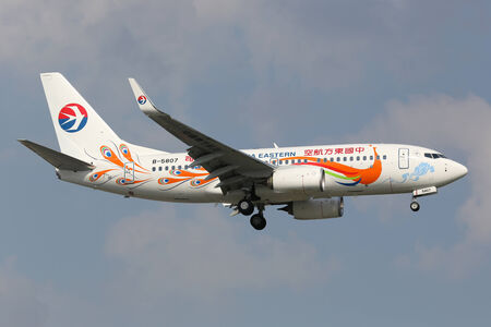 livery: Shanghai, China - September 19, 2013: A China Eastern Boeing 737-700 with the registration B-5807 painted in Yunnan Peacock (orange) special livery approaches Shanghai Airport (SHA) in China. China Eastern is an airline from China. It operates with 353  Editorial