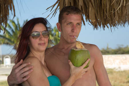 Young people on vacation on the beach drinking from coconut photo