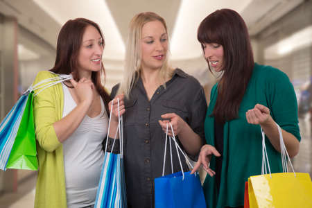 Group of young women with shopping bags talking about their purchase in a shopping mall photo
