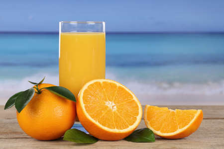 Orange juice and oranges on the beach while on vacation photo
