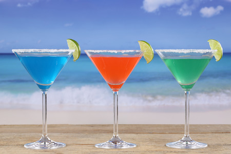 longdrink: Colorful Cocktails in Martini glasses on the beach while on vacation
