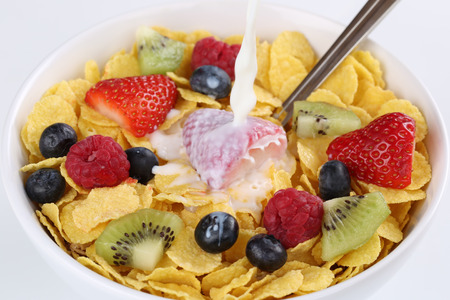 Milk pouring into fruit muesli with strawberries, raspberries, kiwi and blueberries photo