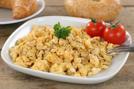 scrambled eggs: Breakfast with scrambled eggs, bagel, croissant and tomatoes Stock Photo