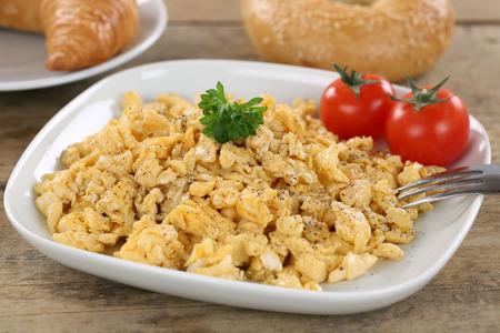 scrambled eggs: El desayuno con huevos revueltos, panecillos, croissant y tomates