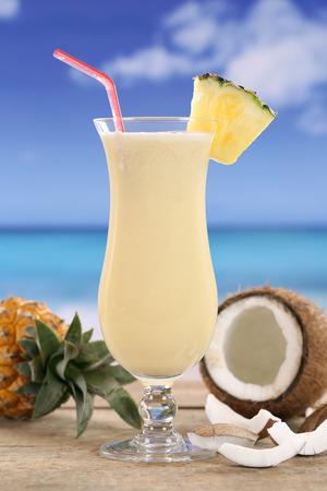 longdrink: Cold Pina Colada cocktail with fruits on the beach while on vacation