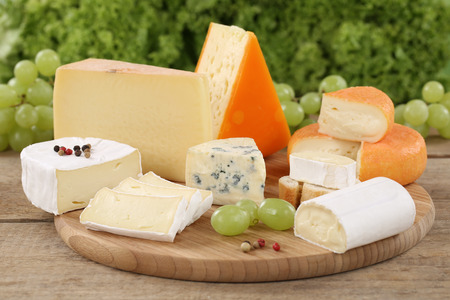 cheese plate: Cheese plate with Camembert, mountain and Swiss cheese on a wooden board Stock Photo