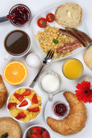 Breakfast table with a cereals, bagels, marmalade, coffee and orange juice from above photo