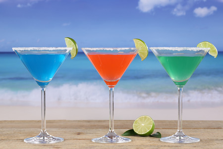 Martini Cocktails in glasses with lemons in summer on the beach