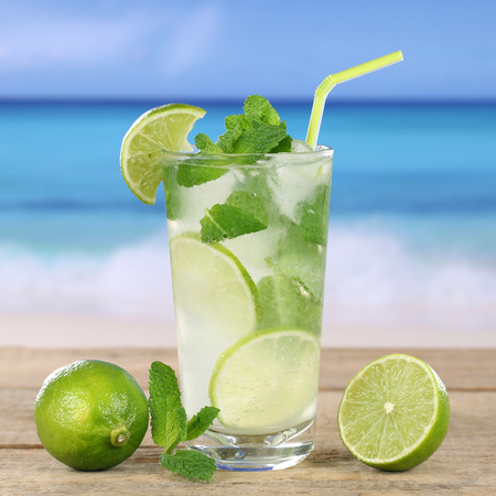 longdrink: Mojito or Caipirinha cocktail drink on the beach while on vacation