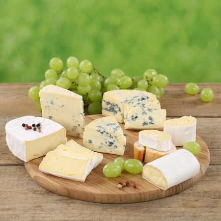 cheese plate: Cheese plate with Camembert, Gorgonzola and Brie on a wooden board Stock Photo