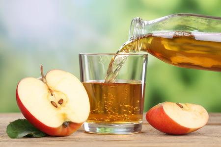 Succo di mela che versa da mele rosse frutti in estate in un bicchiere Archivio Fotografico