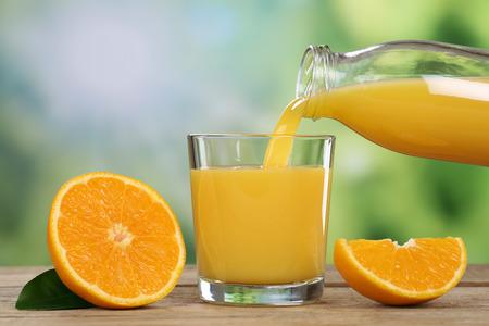verre de jus d orange: Jus d'orange verser dans un verre en été
