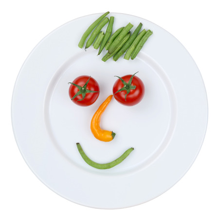 Gezond eten lachende gezicht van groenten op plaat, geïsoleerd op een witte achtergrond Stockfoto