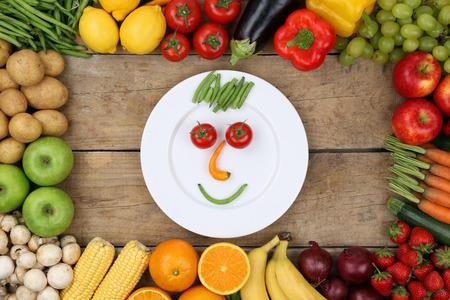 comiendo frutas: Una alimentaci�n sana cara sonriente de verduras y frutas en la placa