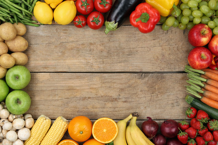 Fresh fruits and vegetables on a wooden board with copyspace Фото со стока