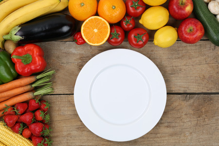 empty plate: An empty plate is framed with vegetables and fruits
