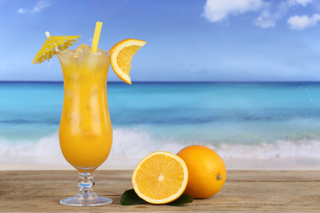 longdrink: Orange fruit cocktail on the beach while on vacation Stock Photo
