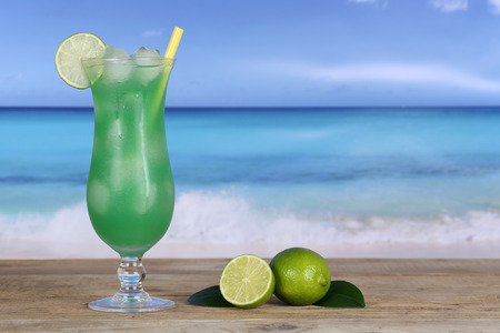 longdrink: Fruit cocktail with limes on the beach and sea while on vacation