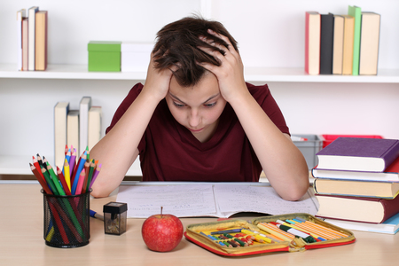 burnout: Young student is desperate while doing homework at school
