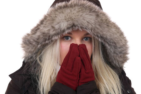 Young woman freezing in the cold in winter with gloves and cap, isolated on a white background